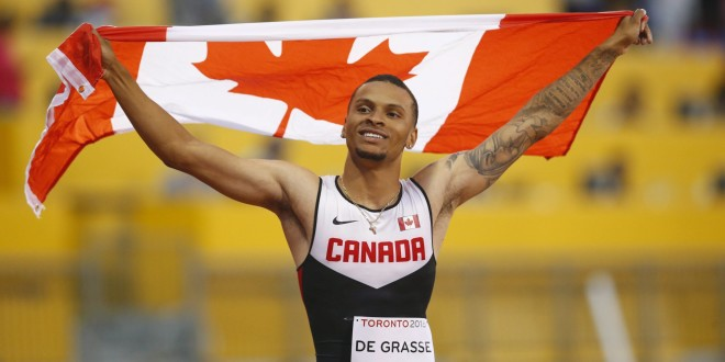 Andre De Grasse, of Canada, holds a flag after he wins the gold medal in the men's 100m final during the athletics competition at the 2015 Pan Am Games in Toronto on Wednesday, July 22, 2015. THE CANADIAN PRESS/Mark Blinch